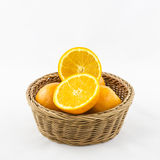 Apelsiner i den isolerade vide- korgen Royaltyfria Foton