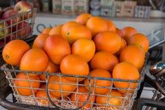 Apelsiner i korg Arkivfoto