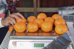 Apelsiner i våg i marknaden arkivfoto