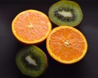 Apelsiner kiwi, snitt på en mörk färg för platta Royaltyfri Foto