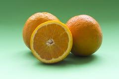 Apelsiner med grön bakgrund Arkivbild