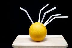 Apelsiner med röret Arkivbild