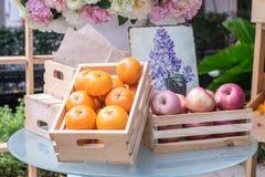 Apelsiner och äpplen i asken royaltyfria foton