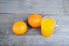 Apelsiner och orange fruktsaft royaltyfria bilder