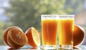 Apelsiner och orange fruktsaft royaltyfria foton