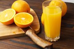 Apelsiner och orange fruktsaft på tabellen arkivbild