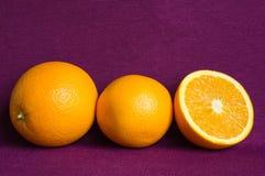 Apelsiner på en violett bakgrund Arkivbilder