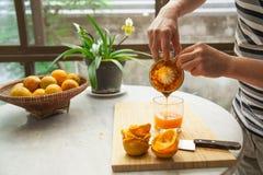 Apelsiner pressas av handen för att göra en ren och sund orange fruktsaft Arkivbilder