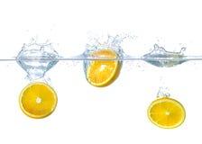 Apelsiner som faller in i vatten med färgstänk arkivbilder
