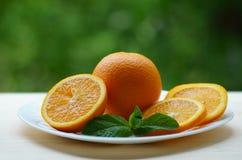 Apelsiner som skivas i cirklar på en vit platta med den hela apelsinen Fotografering för Bildbyråer