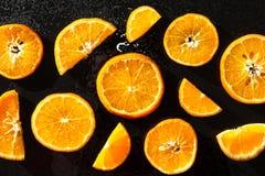 Apelsiner som skivas på en svart bakgrund royaltyfri foto