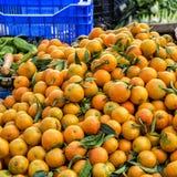 Apelsiner som utanför staplas i ett stånd Arkivbild