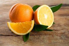 Apelsinfrukt med sidor på träbakgrund royaltyfri bild