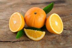Apelsinfrukt med sidor på träbakgrund Arkivfoton