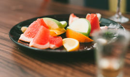 Apelsinskivor, Apple skivor, grapefruktsegment på den svarta plattan Arkivbilder