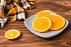 Apelsinskivor på en platta på en trätabell Arkivbilder
