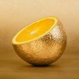 Apelsinsnitt med den guld- peelen på guld- bakgrund Arkivfoto