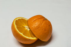 Apelsinsnitt på en halva som isoleras på vit bakgrund Arkivbild