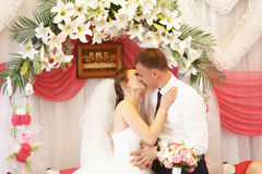 Apenas beijo casado na parte dianteira do altar feita dos lírios Fotografia de Stock
