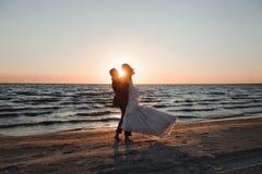 Apenas casado Pares novos bonitos na praia no por do sol imagens de stock royalty free