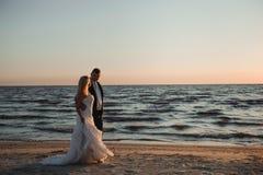 Apenas casado Pares novos bonitos na praia no por do sol imagem de stock