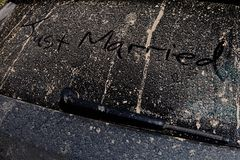 Apenas casado trazado a mano en la parte de atrás de un coche fangoso en un sol foto de archivo libre de regalías