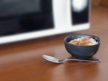Apenas cozinhado na micro-ondas, papa de aveia orgânico autêntico na bacia marrom na superfície da cozinha Com canela e colher fotos de stock