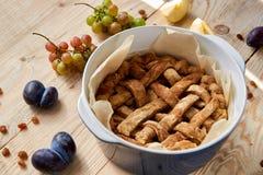 Apenas empanada de manzana hecha en casa cocida en la forma azul de la hornada adornada con las manzanas frescas, las uvas y las  Imagen de archivo libre de regalías