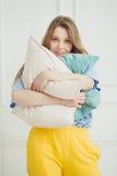 Apenas la muchacha despertada fuera compone soportes con las almohadas Foto de archivo libre de regalías