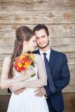 Apenas la pareja casada encendido wodden el fondo Imagen de archivo