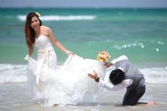 Apenas los jóvenes casados felices juntan la celebración y se divierten en el galán Imagen de archivo libre de regalías