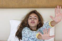 Apenas muchacha bonita despierta del adolescente con la cara divertida de la emoción y el pelo salvaje en la cama fotos de archivo