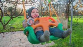 Apenas niño llevado feliz que balancea en un oscilación del patio trasero almacen de video