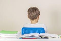 Apenas o assento triste da criança gerencie para trás na tabela com a pilha de livros e de cadernos de escola fotografia de stock royalty free