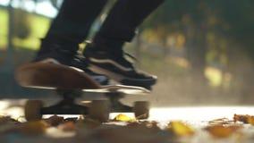 Apenas o homem do skater monta um skate nas folhas caídas fora Foco no primeiro plano Movimento lento filme