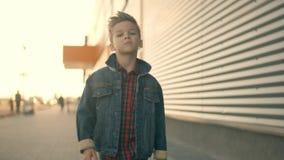 Apenas o rapaz pequeno está andando abaixo da rua e do pensamento Cara de um menino triste sério pequeno que é video estoque