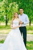 Apenas pareja cariñosa casada del inconformista en vestido y traje de boda en campo verde en un bosque en la puesta del sol Novia Foto de archivo libre de regalías