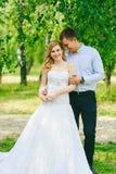 Apenas pareja cariñosa casada del inconformista en vestido y traje de boda en campo verde en un bosque en la puesta del sol Novia Imagen de archivo
