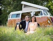Apenas pareja casada feliz en una autocaravana clásica en un campo Foto de archivo libre de regalías