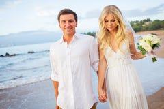 Apenas pareja casada que camina en la playa en la puesta del sol Imagen de archivo