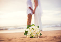Apenas pareja casada que lleva a cabo las manos en la playa Imagen de archivo