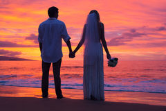 Apenas pareja casada que lleva a cabo las manos en la playa en la puesta del sol Fotografía de archivo libre de regalías