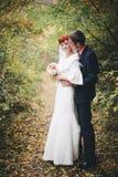 Apenas pareja casada que presenta en un parque del otoño Imagen de archivo libre de regalías