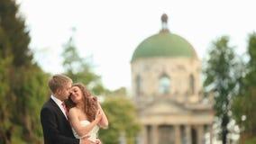Apenas pareja casada sensual que abraza feliz en parque con la iglesia antigua distante en el fondo metrajes