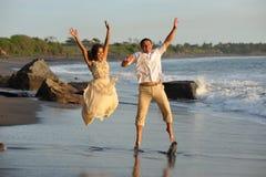 Apenas salto casado feliz de la pareja de los jóvenes Imágenes de archivo libres de regalías