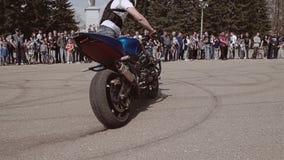 Apenas truco impresionante de la acción en una motocicleta El jinete comienza la raza en la bici en un círculo en el salón del au almacen de metraje de vídeo