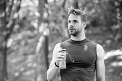Apenas um minuto para descansar a aparência atlética do homem guarda a garrafa com água Equipe o atleta em cuidados da roupa do e fotografia de stock royalty free