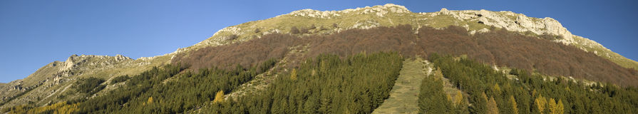 Apennines. Panoramic view of piana del Gran Sasso with blue sky in the background. The Gran Sasso or great stone forms the centerpiece of the Gran Sasso e Monti stock photography