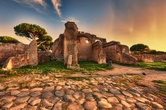 Aperçu de coucher du soleil de rue de pavés ronds dans des ruines antiques d'Ostia photo stock
