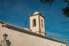 Aperçu de lampe, de mur et de vieux beffroi sous le ciel ensoleillé bleu dans Paraty images stock